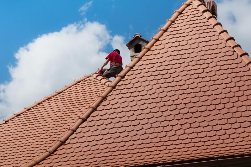 professional roofer working on house roof replacement