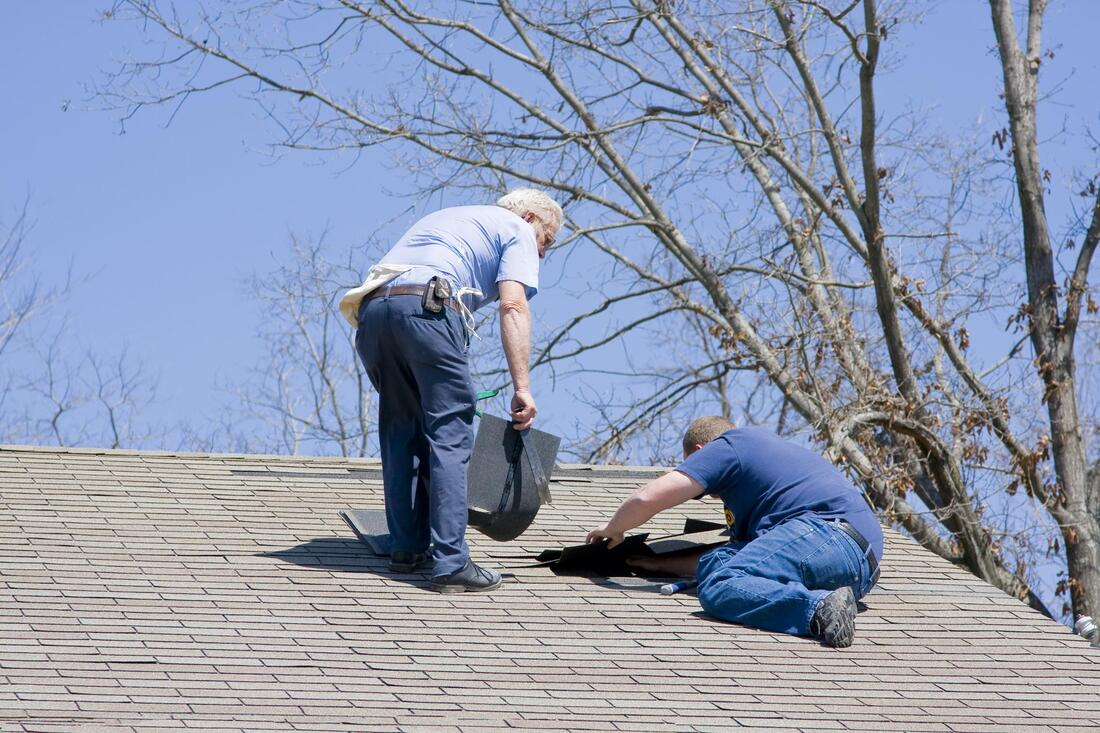 professional roofer working on house roofing